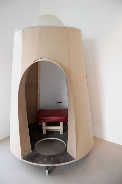 Portable Reading Room is a space made for one person intended for the reading of The Box Man by Kobo Abe. A perambulatory architecture for one, it is intended to mirror the novel, which tells the story of a man who decides to live inside a cardboard box (worn over his head and down to his knees). On castors, the room can be moved (for privacy or for a good reading spot) by pushing off with a foot through the hole in the floor. The work is accompanied by additional reading material.