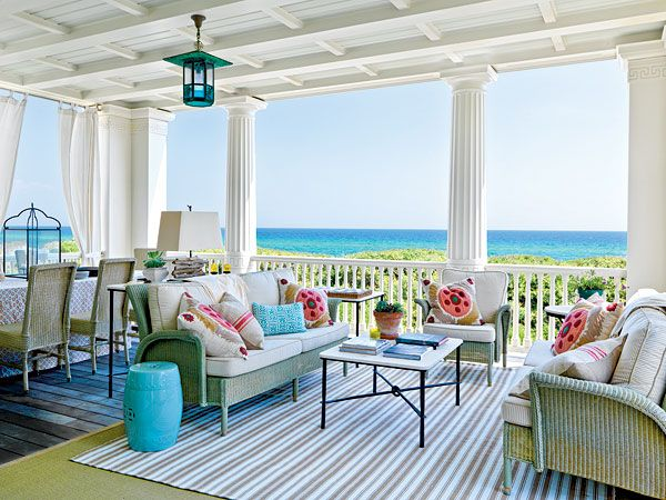 This open air covered deck serves two individual purposes with both a sitting area and a place for dining. A striped indoor-outdoor rug is layered over a seagrass rug to define the two spaces. The classic architecture of this Seaside, Florida home (Photo: Jonny Valiant)  Love it