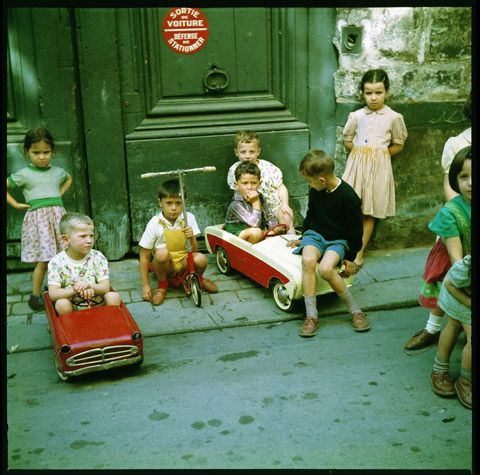 Paris in 1960 by Jean Jéhan Des enfants font la course de voitures à pédales, avec une trottinette dans les starting-blocs devant une porte cochère. 1960s