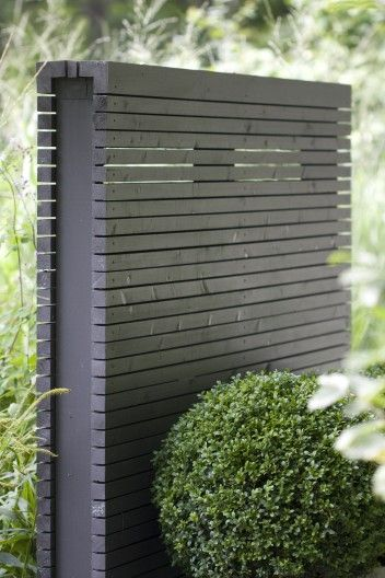 Dark colored, anthracite wooden fence that works well as screen or background for planting in light colours