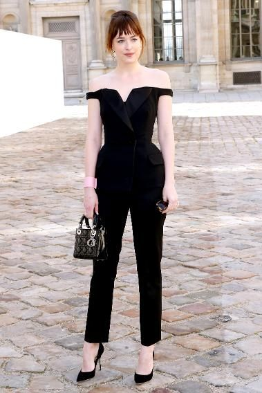 The actress arrived at Dior's fall 2015 show looking nothing like 50 Shades of Grey's Anastasia Steele and everything like a bonafide movie star. And the best part is, she pulled off a difficult to wear high-fashion look like it's no big thing. A jumpsuit is tricky, but an off-the-shoulder jumpsuit? That's trickier. Throw in the structured, exaggerated hips and this could have been a disaster on anyone else. But thanks to Johnson's ladylike accessories—classic pumps, a mini Lady Dior ...