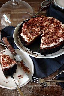 Chocolade-crèmetaart  250 g Oreo koekjes 95 g boter 150 g pure chocolade 65 g fijne kristalsuiker 3 el maïzena 2 eierdooiers 350 ml melk 1 tl vanille-extract 250 ml slagroom  cacaopoeder, voor het bestrooien geraspte (melk)chocolade, voor het bestrooien