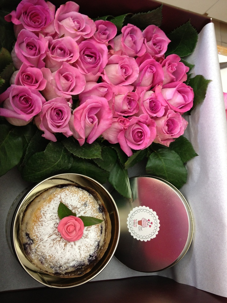 Box with mini cake and fresh flowers
