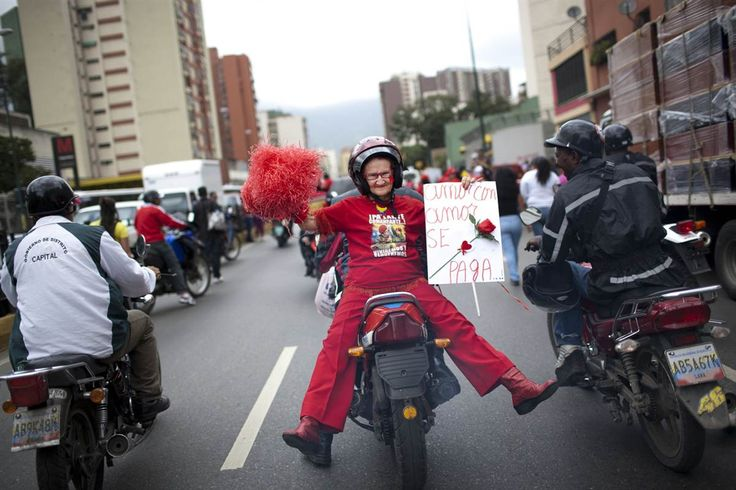 """Ariana Cubillos / AP  A supporter of Venezuela's President Hugo Chavez, Marlene Vanegas, 72, known as """"Little Red Riding Hood,"""" rides on the back of a motorbike holding a homemade signs that reads in Spanish; """"Love is paid with love,"""" during a rally marking International Women's Day in Caracas, Venezuela on March 8."""