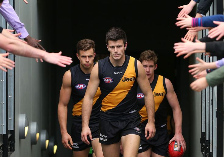IlPost - Da sinistra,Brett Deledio,Trent Cotchin e Matt White dei Tigers entrano in campo durante la partita di football australiano AFL tra i Richmond Tigers e i Fremantle Dockers al Melbourne Cricket Ground di Melbourne, Australia, 21 luglio 2013. (Michael Dodge/Getty Images)