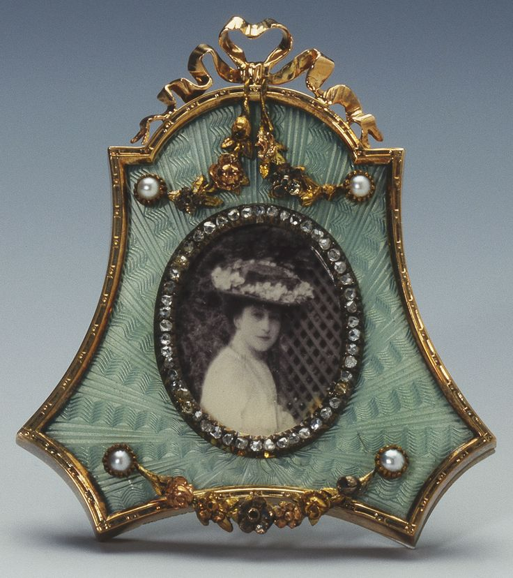 Fabergé red gold photograph frame with concave sides and domed top, aquamarine enamel over sunray engraving, the border with applied ribbon cresting and hung with swags set with pearls. Workmaster Viktor Aarne. Oval bezel is edged with rose diamonds and inset with a photograph of Maud, Princess Carl of Denmark.