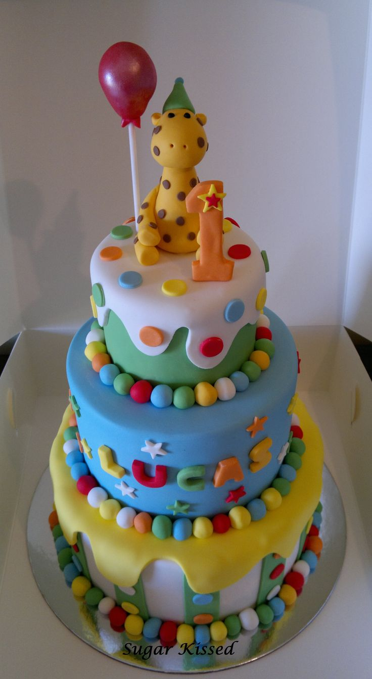 A 3 tier giraffe cake created by Shandi Sansom from Sugar Kissed. Featuring a hand crafted giraffe topper, a shiny red balloon and a number 1. Please visit my facebook page to see more of my work: www.facebook.com/sugarkissedshandi