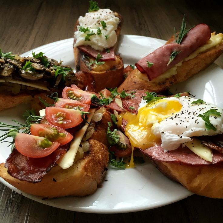 A plate of crostinis, topped with cherry tomatoes, ham, bacon, garlic mushrooms, cheddar, bechamel & poached eggs.