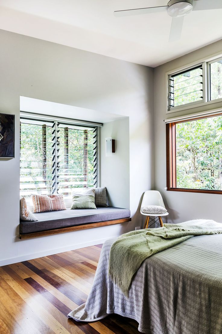 """The main bedroom is simply furnished, with remilled mixed-hardwood flooring and plenty of natural light streaming through the louvre windows. """"The simple colour scheme picks up on the colour of the granite boulders and the rainforest,"""" says Chris.  Plasterboard **walls** painted in Dulux White Duck from [Dulux](http://www.dulux.com.au/ target=""""_blank""""). Window seat **fabric** and **cushions** from [Warwick Fabrics](http://www.warwick.com.au/ target=""""_blank"""")."""
