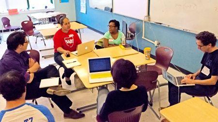 group of teachers sitting in a circle around desks
