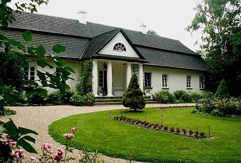 """Dwór w Glanowie, odbudowany w 1863 roku. Dworek klasycystyczny,  """"typowy polski dworek"""" leży na wzniesieniu i zawsze otoczony jest parkiem. Jest parterowy, najczęściej ma czterospadowy dach łamany kryty gontem lub dachówką."""