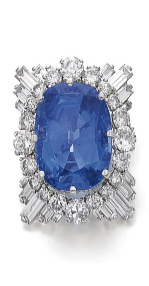 Sapphire and diamond clip, Cartier Centring on a cushion shaped sapphire, within a border of single- and circular-cut diamonds, the corners set with radiating baguette diamonds, signed Cartier, numbered, French assay and maker's marks.