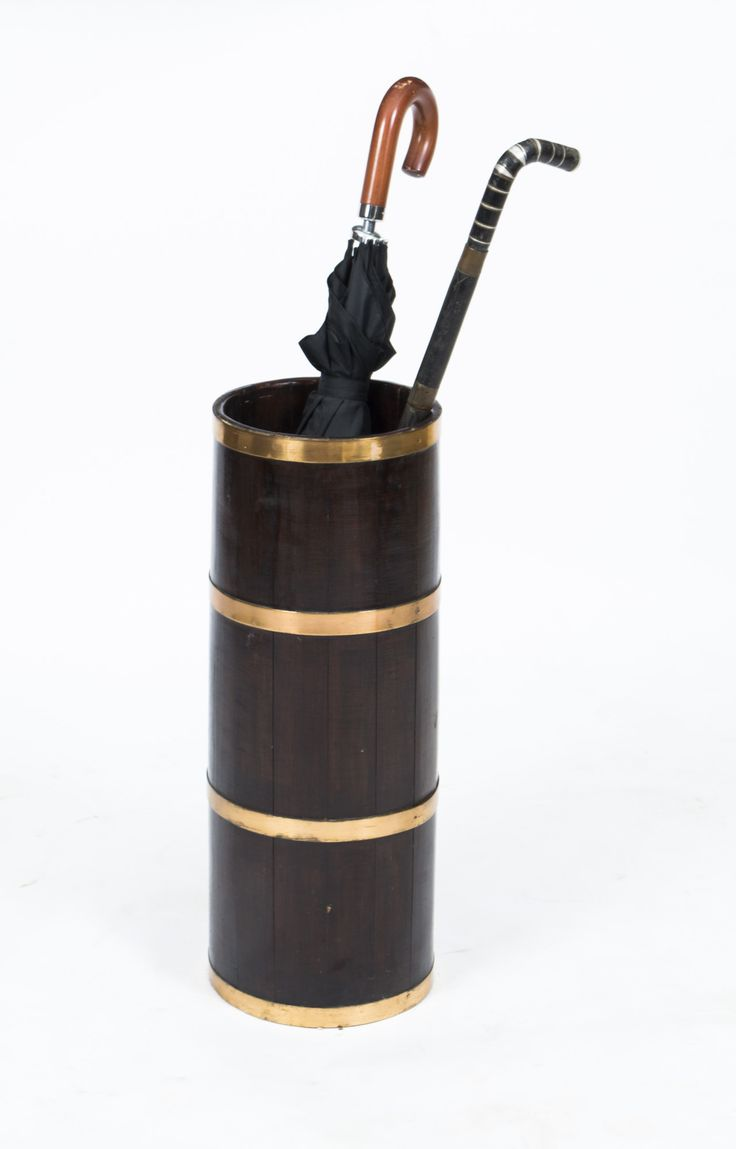An antique oak brass umbrella stand highly useful for English weather.