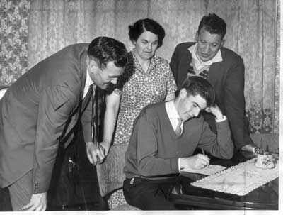 Peter Lorimer signs his first contract watched by his parents and Don Revie.