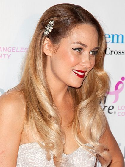 Lauren Conrad's hair accessory with long, curled locks, a black cat eye and red lipstick | allure.com