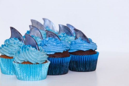 """shark week ~ fins are fondant, put in freezer for a bit and hand-cut, then brushed with edible """"pearl dust"""" from Michael's craft store."""