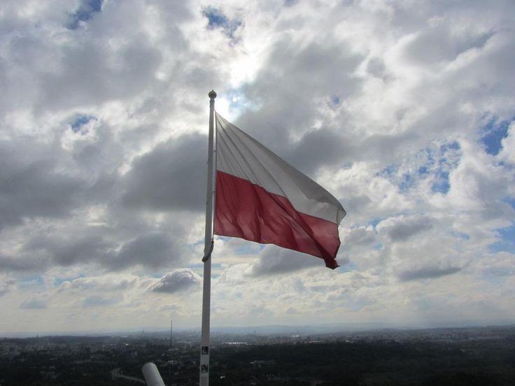 Bandera polaca contra el cielo de Cracovia