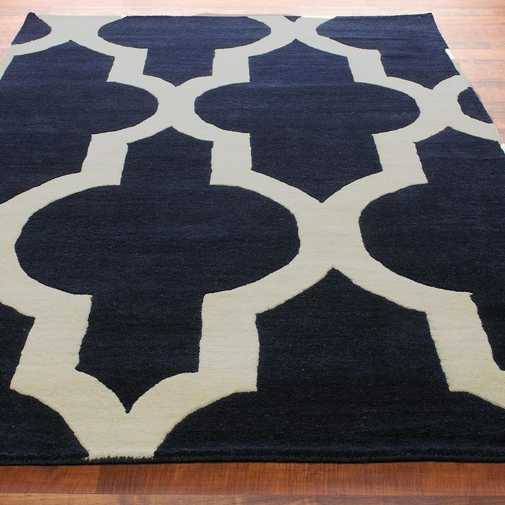 Oversized Moroccan Tile Hand Tufted Rug: 2 ColorsAn oversized, bold Morrocan tile pattern is stunning in your choice of Navy with Cream or Rusty Red and Cream trimmed in Cocoa. Hand-tufted in 100% wool, this rug will make a statement in your space. Imported. 100% wool
