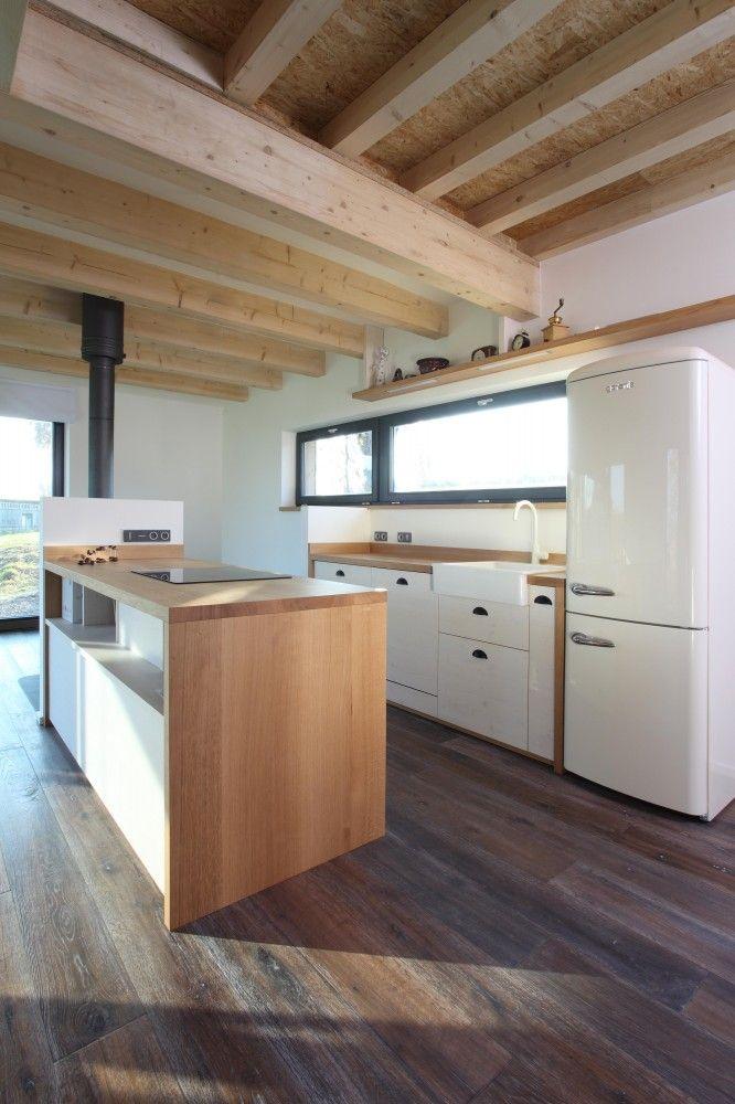 cocina rústica, casa rural rehabilitada, con isla central para zona de cocción, frigorífico vintage, suelo de parquet