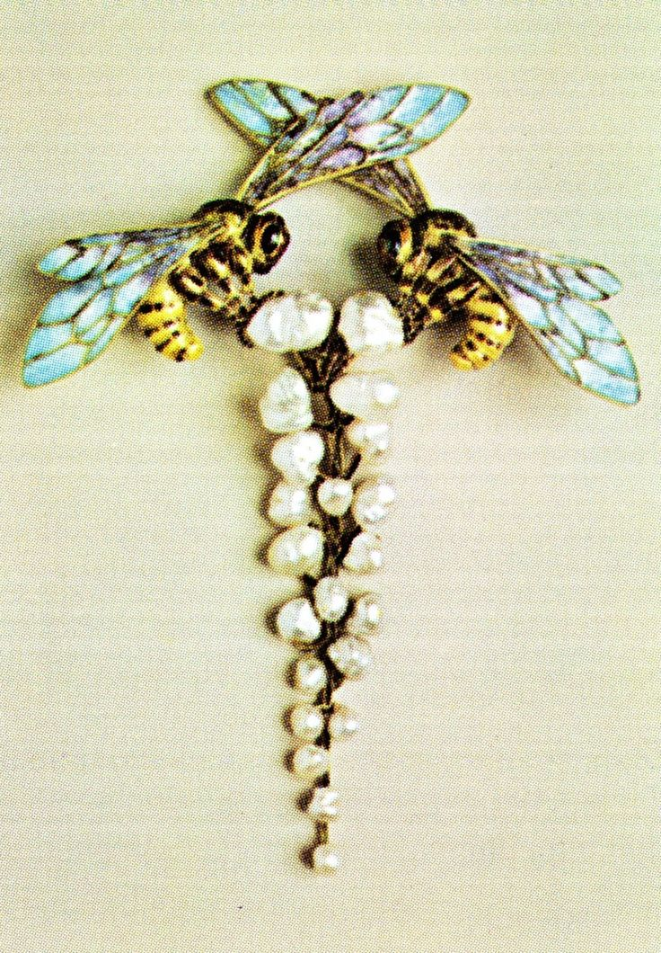 Liénard - An Art Nouveau gold, pearl and enamel brooch, French, circa 1905 or later. Designed as two confronted bees alighting on a wisteria frond. Signed Liénard. Source: From Slave to Siren: Dora Jane Janson. #Lienard #ArtNouveau #brooch