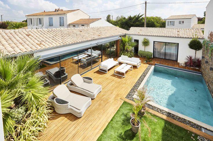 Une terrasse en bois autour d'une belle piscine. De grandes baies vitrées pour amener de la luminosité dans le salon. Des palmiers pour l'esprit exotique. #menuiserierideau
