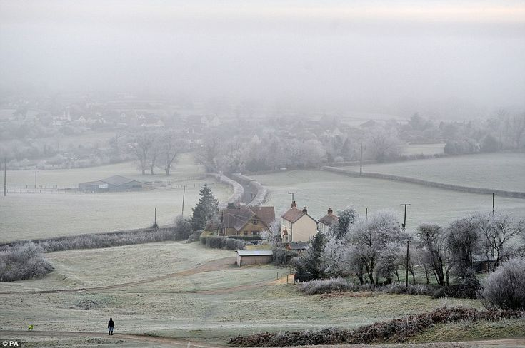 A person looks out over a foggy scene near Dursley in Gloucestershire as mist hangs over the village