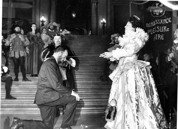 """An actress of the Renaissance Pleasure Faire touring company playing Queen Elizabeth I """"knights"""" Adrian V.O. Small, captain of the Golden Hinde II, at San Francisco City Hall on March 10, 1975. Photo: Susan Ehmer, The Chronicle"""