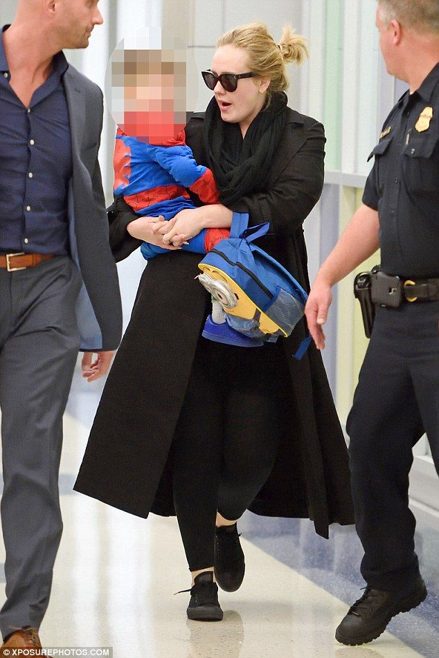 Family trip: Adele carried her three-year-old son Angelo through JFK airport in New York on Thursday after jetting in for the next stop on her promo tour