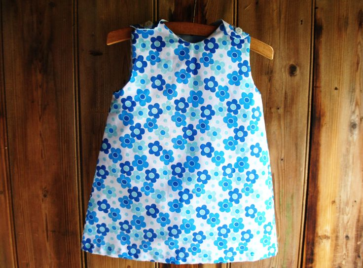 1960S BLUE DAISY DRESS  12.00 1960s style blue daisy shift dress 9-12 months  Blue daisy-patterned shift dress with white daisy button fastenings on the shoulders. This is a reproduction 1960s shift dress hand-crafted from vintage fabric. Super sweet for summer.    Circa: 1960s fabric