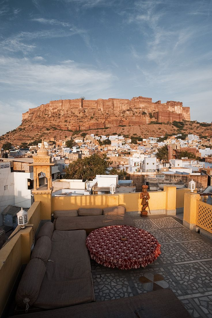 The Mehrangarh fort in Jodhpur and blue Brahmin homes viewed from a rooftop restaurant.- Jodhpur, Rajasthan, India - Daily Travel Photos