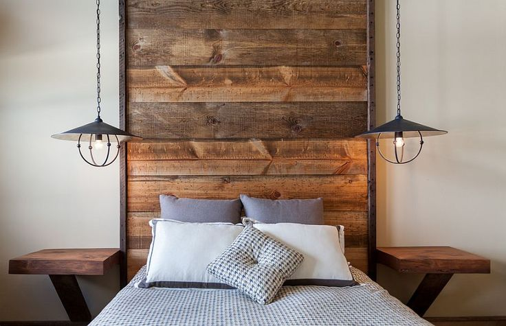 Floor-to-ceiling headboard with wooden planks in the rustic bedroom [Design: High Camp Home]