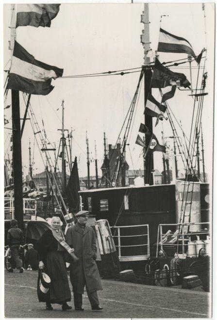Vlaggetjesdag in de Scheveningse haven. Een Schevenings echtpaar neemt een kijkje bij de gepavoiseerde schepen. 1962 Anefo Nationaal Archief #ZuidHolland #Scheveningen