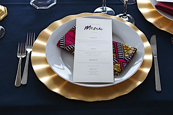 African Inspired details | Custom Ankara print Fabric table napkins | Big Dawg Party Rental table linens and plate setting | tapered candles | custom menu cards | Floral centerpieces by Barbara Flowers
