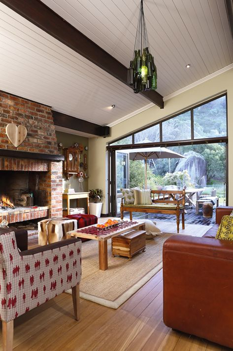 Folding sliding doors are installed to maximise light and the view of the mountain, and in summer it opens up and the fireplace is used as a braai.