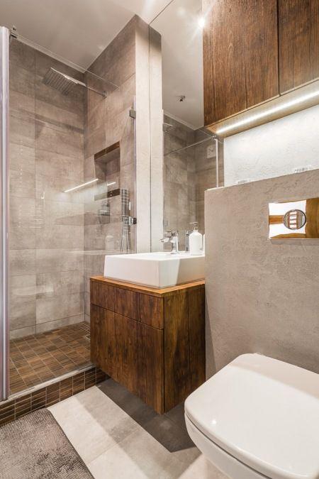 Nowoczesna łazienka w ciemnych kolorach, w której dużą rolę odgrywają tafle szkła. Podświetlenie oraz geometryczna forma mebli i elementów wyposażenia podkreślają klimat łazienki.