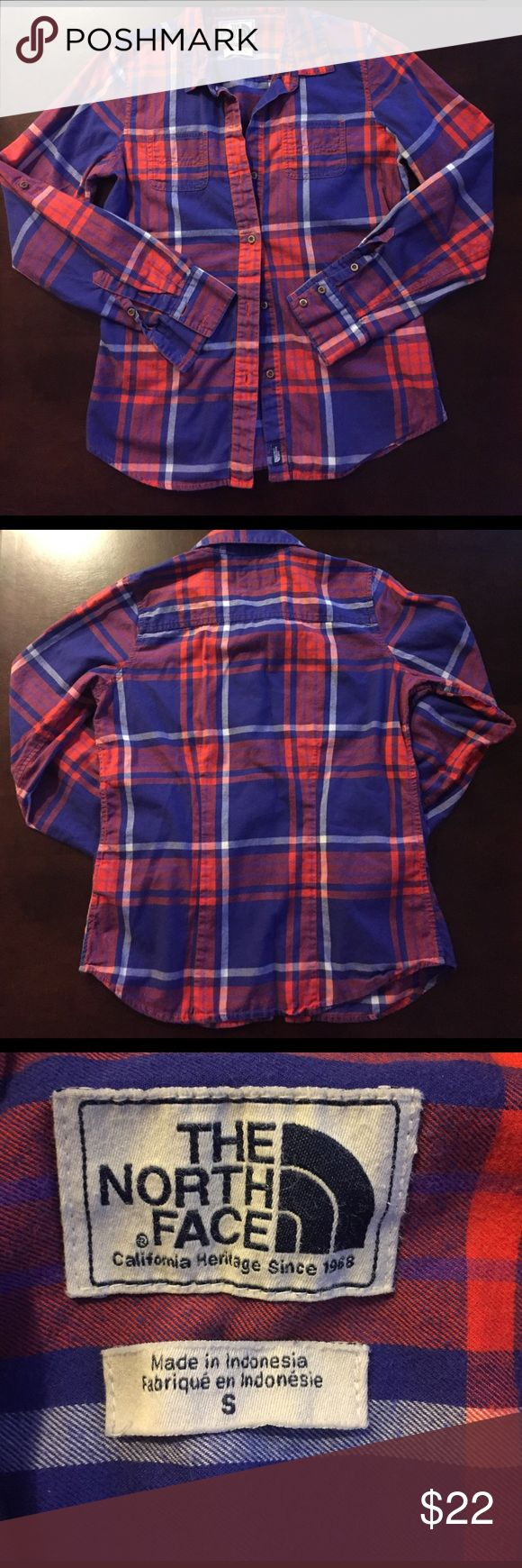 The North Face Ladies Plaid Flannel Shirt Ladies Plaid button-up fitted flannel shirt.  The fabric features a beautiful red, white, and blue Plaid that is perfect for patriotic occasions!  The fabric is 100% cotton and has that comfortable feel of your favorite shirt.  Has wooden buttons in the front and on the cuffs.  The sleeves can be rolled up and secured in place with a tab and button fastener.  Worn and washed a few times. The North Face Tops Button Down Shirts