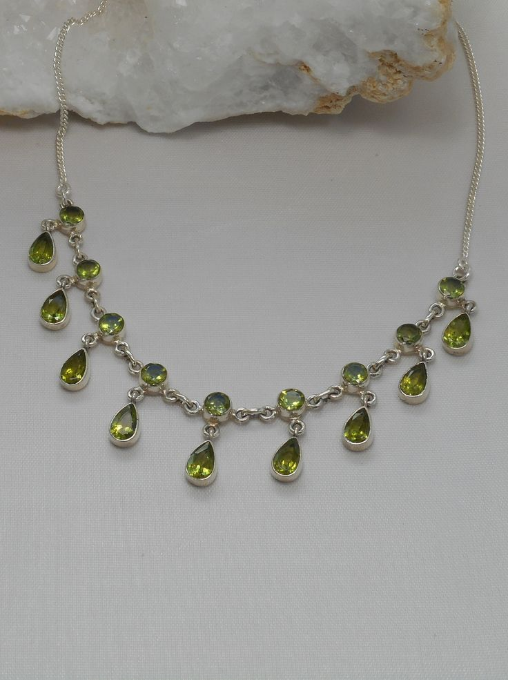 "Eighteen faceted dangling Peridot gemstones, bezel-set in 925-hallmarked sterling silver on a delicate chain. Length: 16-17""+ Lobster claw clasp. Largest center vertical dimension: .75"""