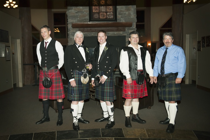 A row of international men at the grand fireplace in the reception area of the lodge.