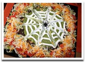 Spooky Spider's Nest: Spider Web 7-Layer Dip    This is one of those wonderful Halloween party appetizers that comes together in about 10 minutes, can be made ahead of time, and will wow everybody at your Halloween dinner party or party. The presentation has a ton of effect without a ton of work.