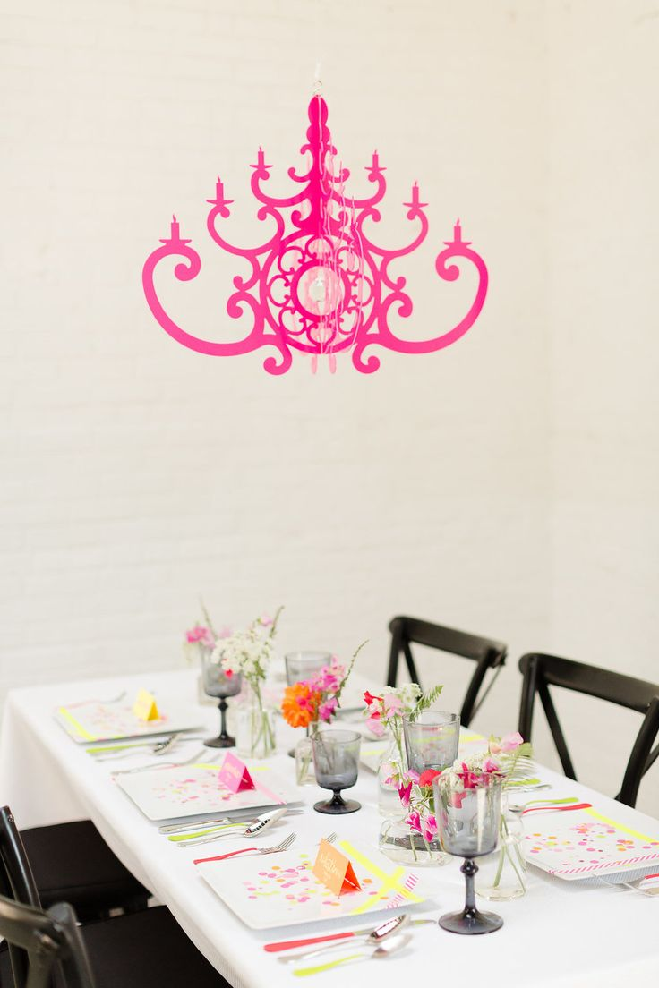 Chandelier Decor for Chic and Modern Weddings and Parties of all Kinds. Hot Pink Chandelier is shown over a neon color styled tablescape. From Chandelier by NK - as seen on www.BrendasWeddingBlog.com