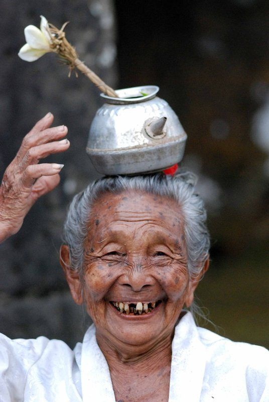 Photographer's caption: Old lady at a temple in Indonesia [Indounik: I believe this lady is a mangku - Balinese Hindu priest - and that's holy water in the vessel on her head. Photographer - Tilde Nielsson on Travellerspoint.]