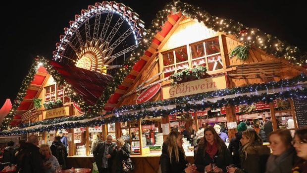 Visitors walk among stalls at the annual Christmas market at Alexanderplatz in Berlin on the market's opening day.