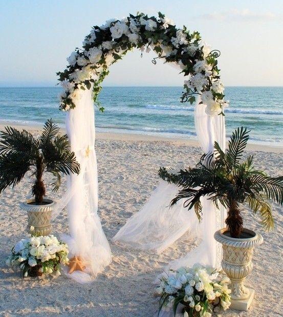 Telas blancas y flores para decorar el arco de la ceremonia en la playa