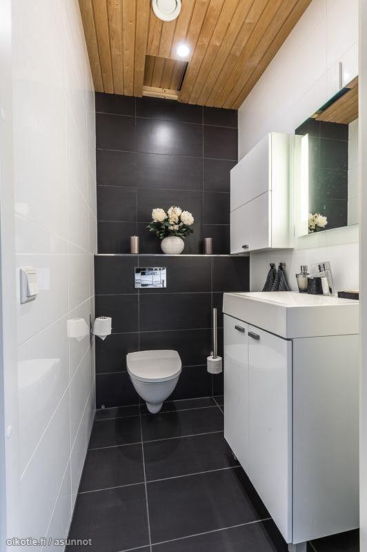 kellarikerroksen vessa. tumma lattia, valkoista samaa kaakelia kuin kylppärissä.. Joku allaskaappi + peili