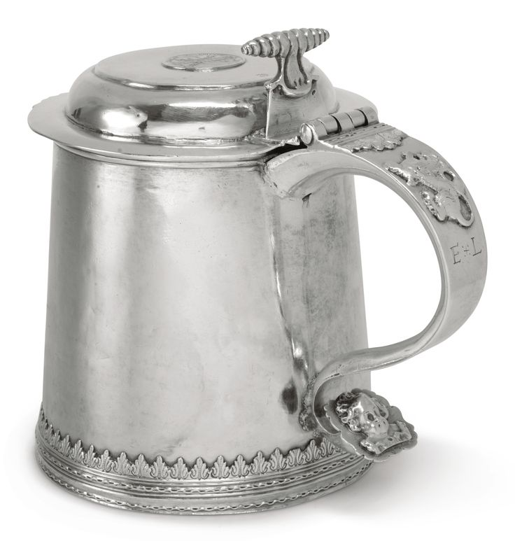 A rare American silver tankard, Koenraet Ten Eyck, Albany, NY, circa 1710 - with cut-card foliate and meander wire base bands, the front engraved W/EE in script, the flat top cover with shaped lip, inset coin, and corkscrew thumbpiece, the handle with applied lion rampant and cherub's head terminal and engraved with block initials E*L, marked on cover near thumbpiece K TE (conjoined) height 7 in.