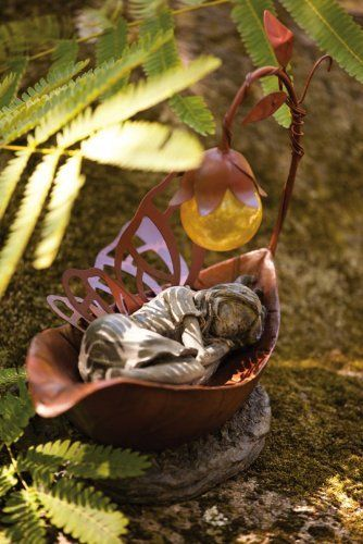 """11"""" Inspirational Statuary Dreamer Fairy Solar Power Outdoor Garden Figure by Evergreen. $54.99. Solor Power Fairy Item #842307Add a touch of whimsical charm to your garden or patio with this delightful fairy figureFeatures a fairy sleeping in a metal leaf with a solar power floral lampDimensions: 6""""L x 6""""W x 11.1""""H Material(s): resin mix/metal"""