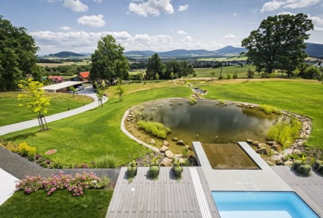 """Na konci """"plavecké dráhy"""" voda spadá z bazénu do přírodního jezírka, kde se daří vodním rostlinám i rybám"""