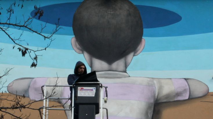 L'artista francese Seth e sullo sfondo il suo murale, Il bambino redentore. -