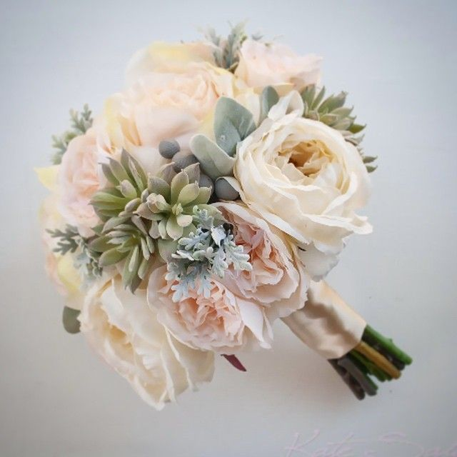 our newest arrangement of peach roses and ivory peonies with succulents dusty miller lambs ear and silver brunia by kate said yes weddings