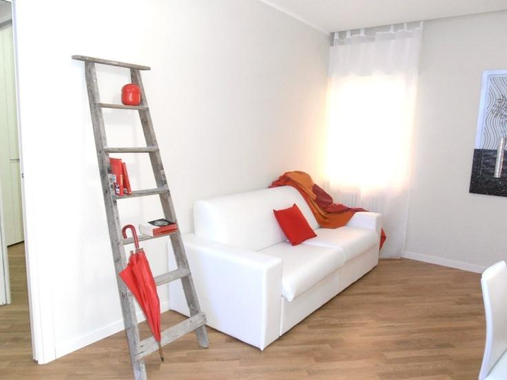 Salotto. Cuscini rossi e scala porta oggetti